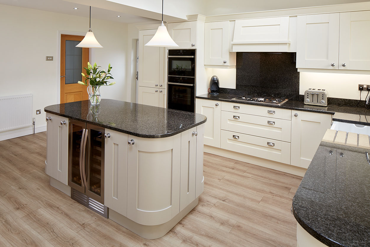 Panoramic view of a white/cream kitchen with fitted furniture and island unit.