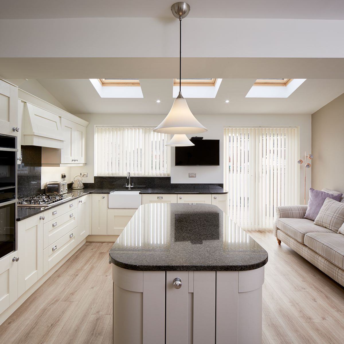 Modern white kitchen with black granite worktop.