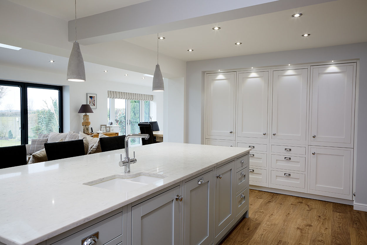 Long view of a open plan kitchen breakfast bar.