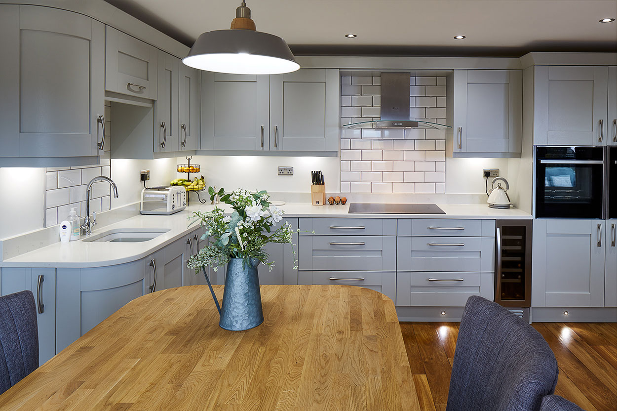 White coloured kitchen, with hardwood island unit.