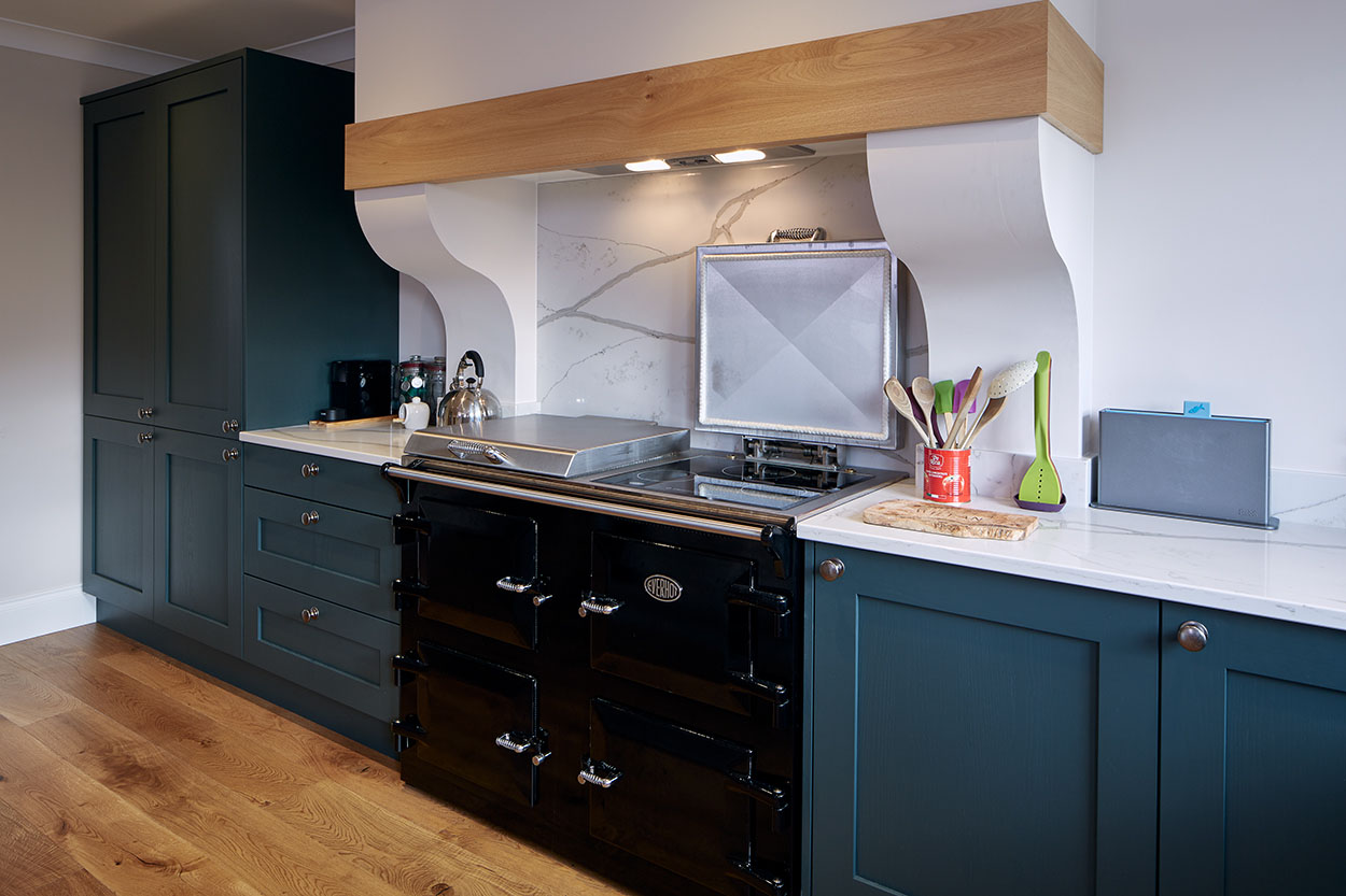 Teal kitchen with integrated double stove and marble worktop.