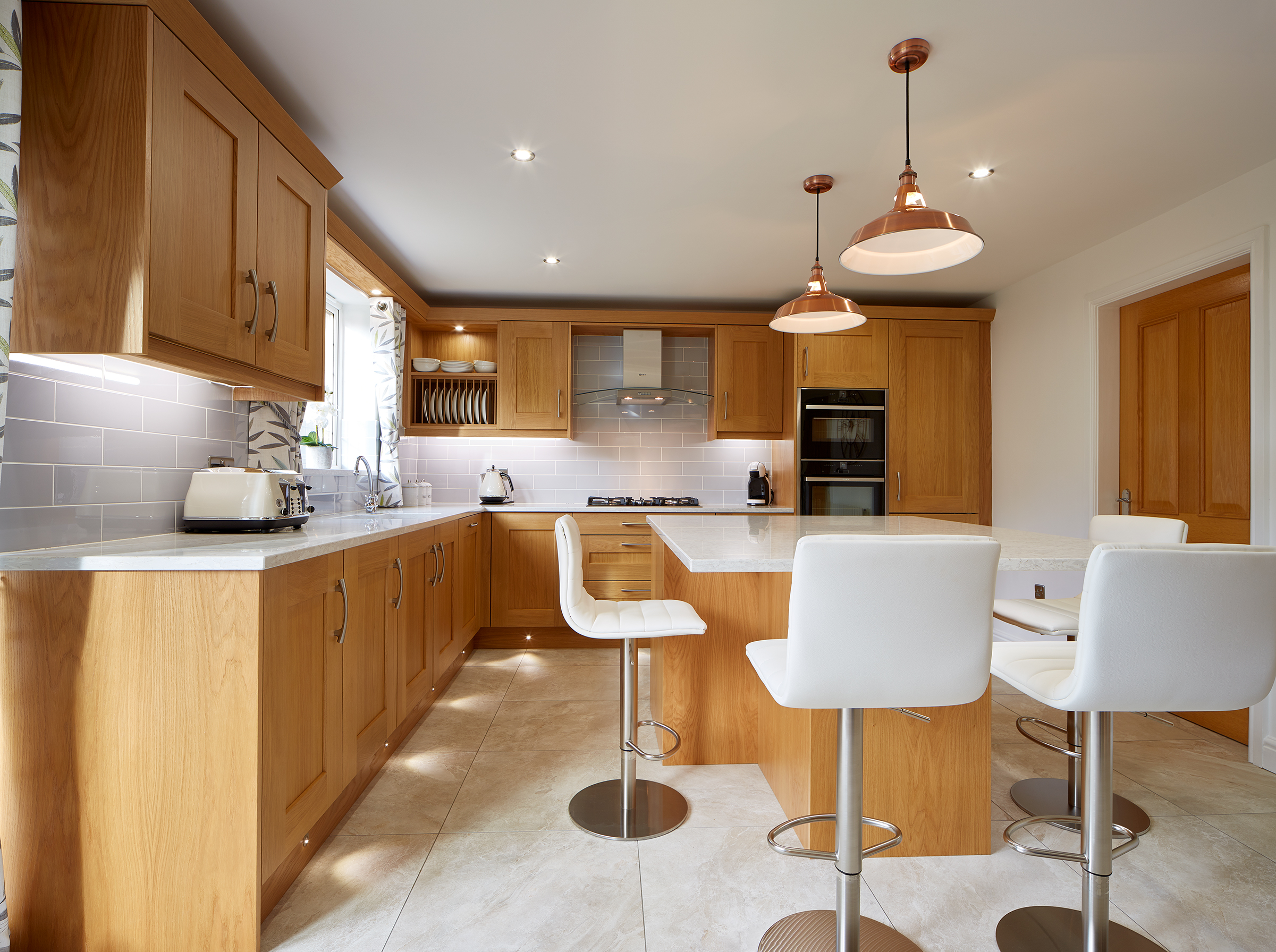 Hardwood oak kitchen with white worktops.