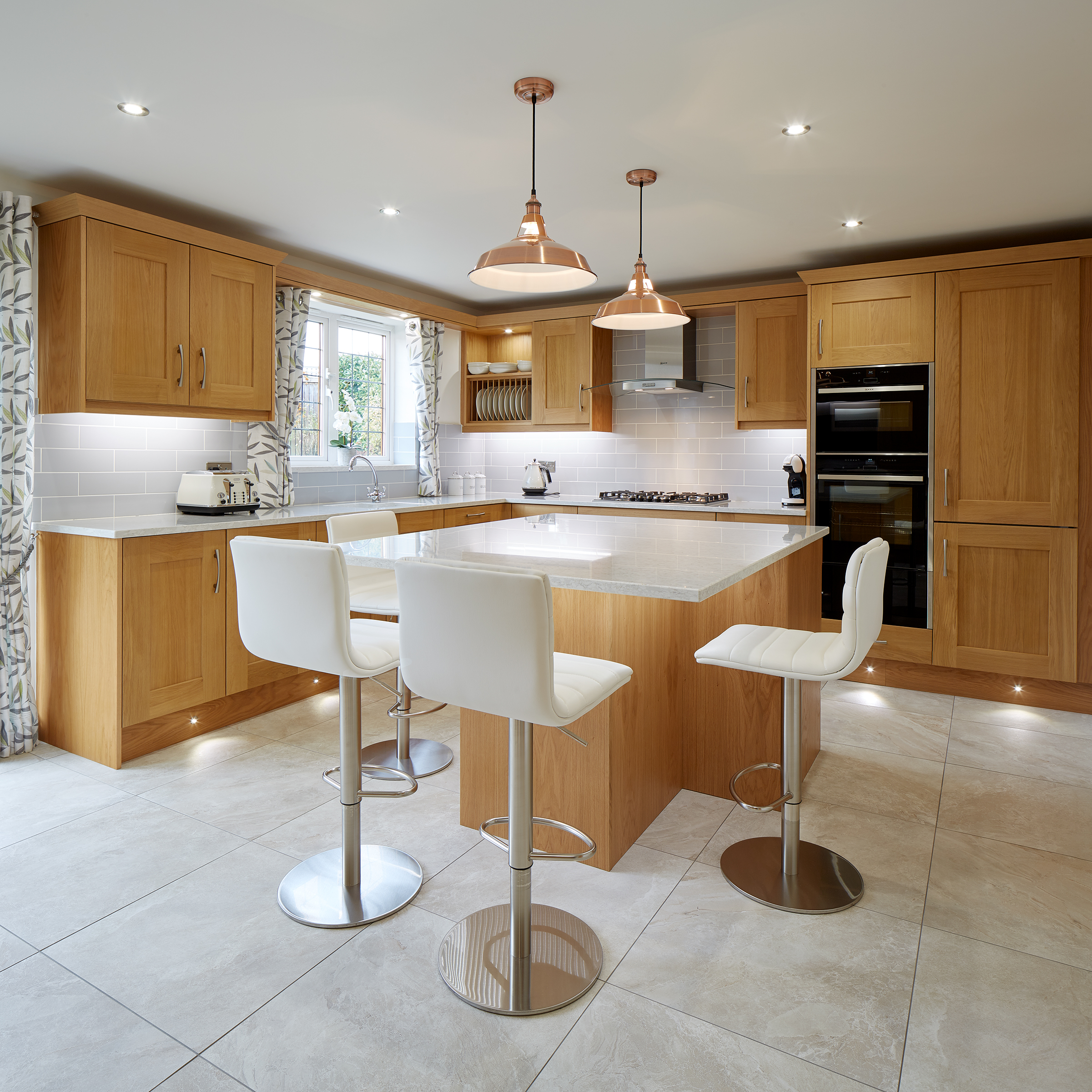 Full view of a oak hardwood kitchen with white granite worktop.