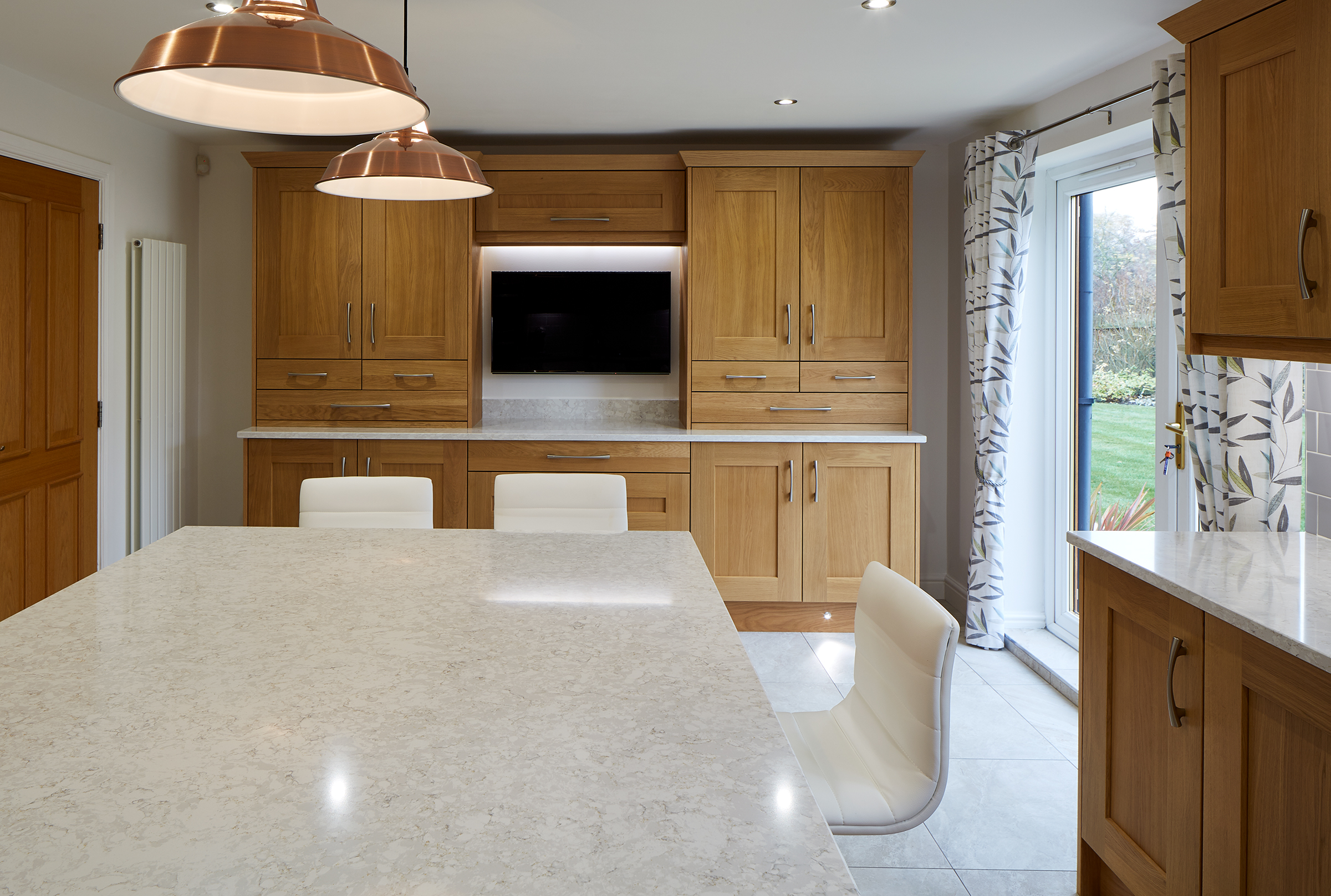 White granite worktop island unit in hardwood kitchen.
